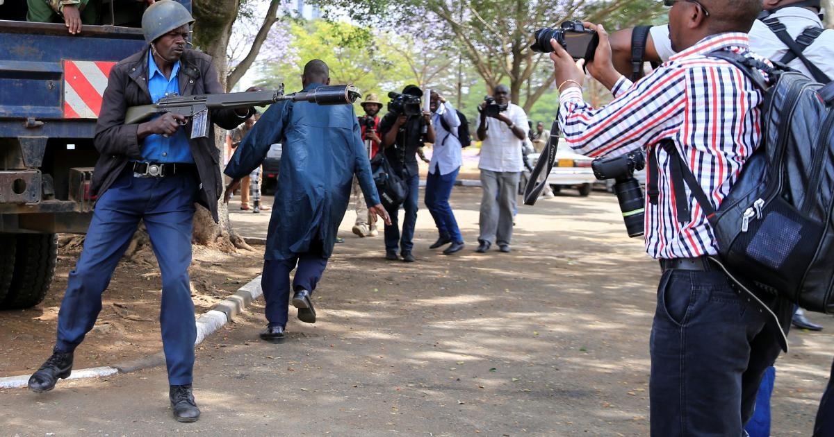 A police officer prepares to launch a teargas canister as journalists take photos. 36 journalists have been attacked in the line of duty between January and April 2020.