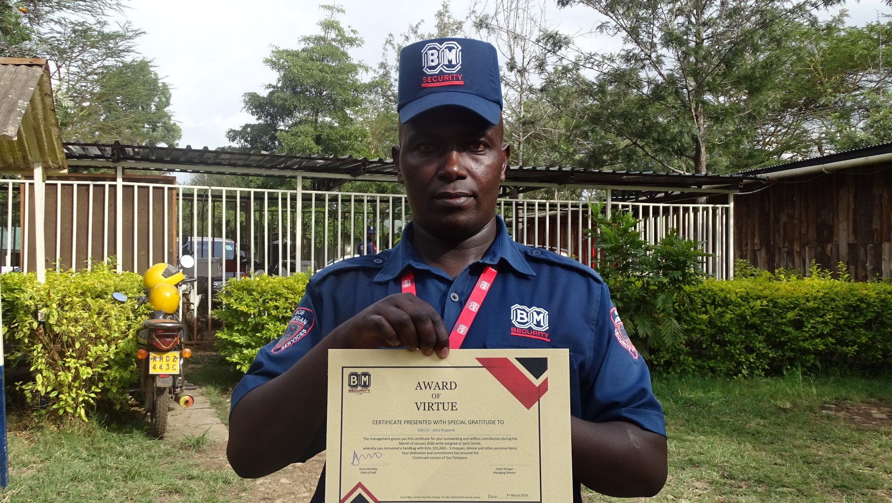Security Guard Joseph Mugendi poses with a certificate after being awarded on March 17, 2020