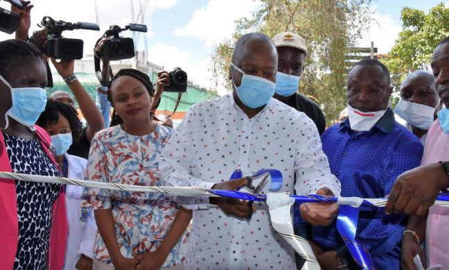 Health CS Mutahi Kagwe launches the Kenyatta National Hospital (KNH) Diagnostic and Reporting Centre, Nairobi in February 2020 as Health CAS Dr Mercy Mwangangi (behind) watches
