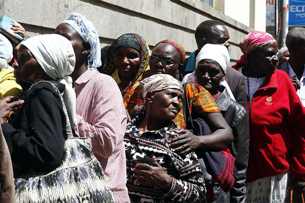 Elderly people queue outside the Kenya Commercial Bank in Nakuru on March 28, 2017 to receive their Sh2, 000 monthly stipend.