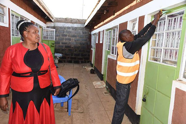 Census enumerator Athnus Kandie slides a 'Call Card' into a house whose occupant is reported to have been inside but refused to open the door for the officials in Shauri Estate in Eldoret Town, Uasin Gishu County on August 25, 2019. Looking on is Veronica Njeri, a village elder.