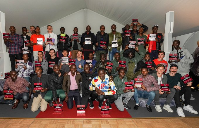 The 41 pacemakers who helped Eliud Kipchoge attain victory holding up their signed trophies.