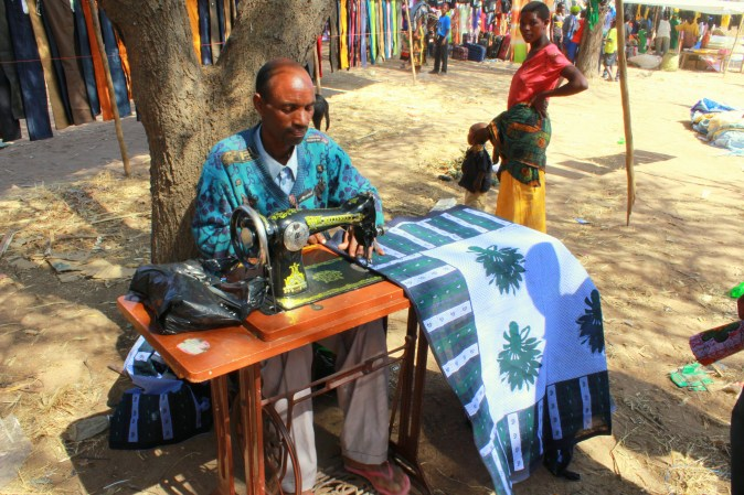 A tailor sits under a tree sewing garments from colorful fabrics.