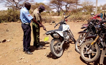 Police officers assess the motorbike that Ngaremara Senior Chief Stephen Mwangola was riding when he was hit and killed by a lorry at Kambi Garba area on Isiolo-Moyale highway on August 30, 2019.
