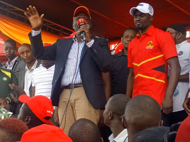 DP Ruto flanked by Jubilee candidate McDonald Mariga addressing the crowd in Kibra on Sunday, October 27.