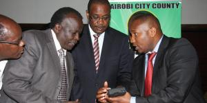 A photo of JamboPay CEO Danson Muchemi (Right) with former Nairobi County Governor Evans Kidero (Centre) and Mt. Kenya Matatu Owners Association Chairman Michael Kariuki during the launch of e-payment for county's services July 24, 2014, in Nairobi.