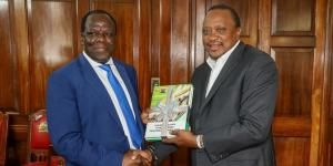 Kakamega Governor Wycliffe Oparanya (l) hands President Uhuru Kenyatta the Sugarcane Taskforce Report on February 24 at State House Nairobi..jpg