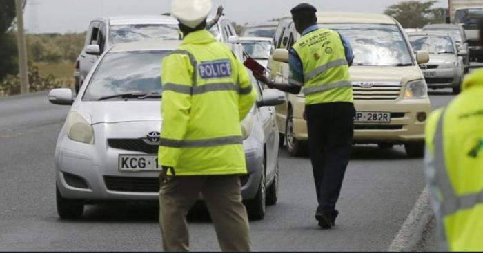 Police officers conduct a transport and road safety inspection of vehicles along a road.