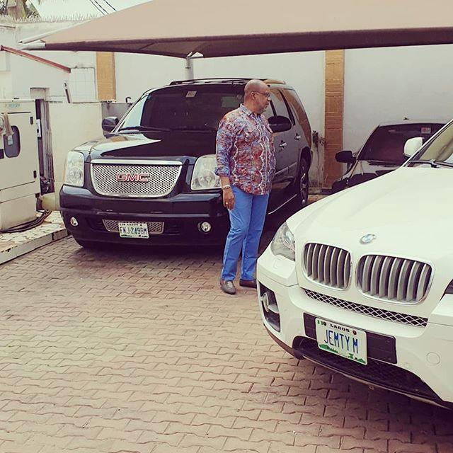 Emmy Kosgey's husband, Apostle Anselm Madubuko, poses for a photo alongside a BMW and an SUV on Friday, March 6, 2020