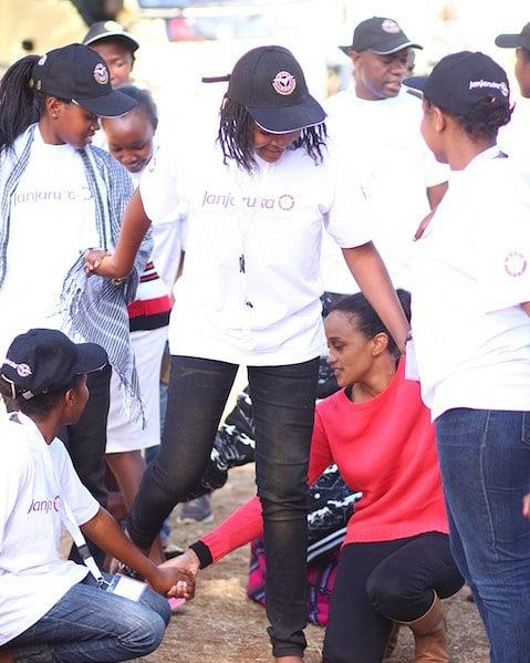 First daughter Ngina Kenyatta (squatting) participates in outdoor games with some beneficiaries of The Kenyatta Trust.