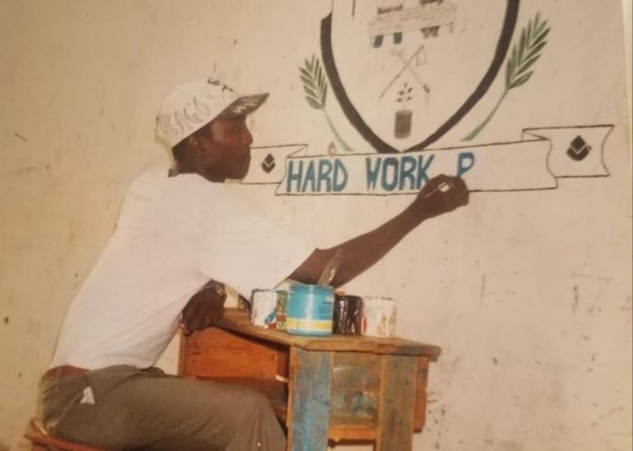 16-year-old Willy Mtuva painting a school logo in his hay days.
