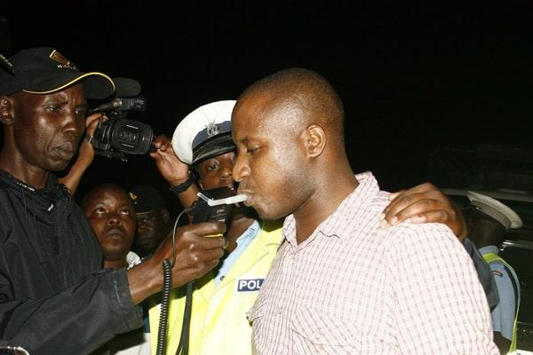 Police officers issue a breathalyzer test to a motorist in Kisumu.
