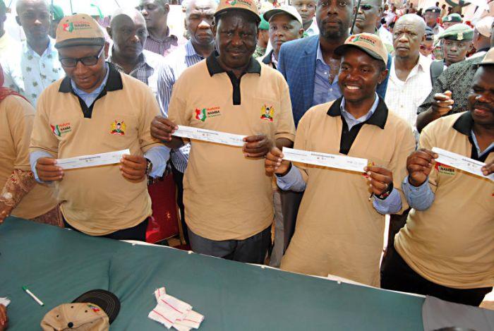 Opposition leader Raila Odinga, ICT CS Joe Mucheru and Mombasa Deputy Governor Joseph Kingi display NIIMS registration slips during the launch of Huduma Namba at Shikadabu, Mombasa in April 2019