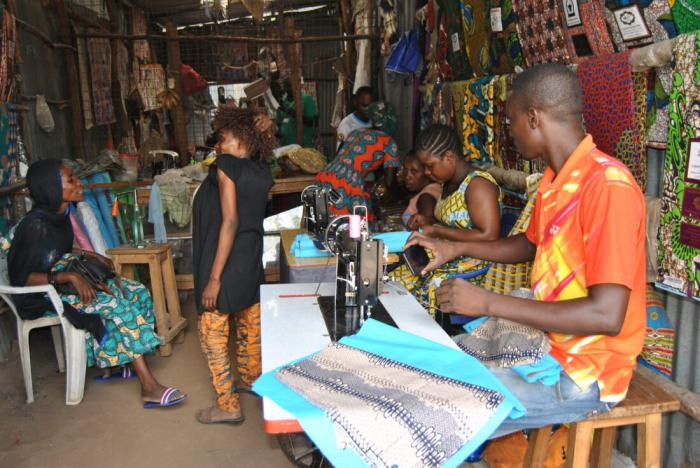Biclere (standing) talks to a client at her shop while her employees work on other clothes.