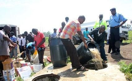 Police officers getting rid of illicit brew. Photo: Standard.
