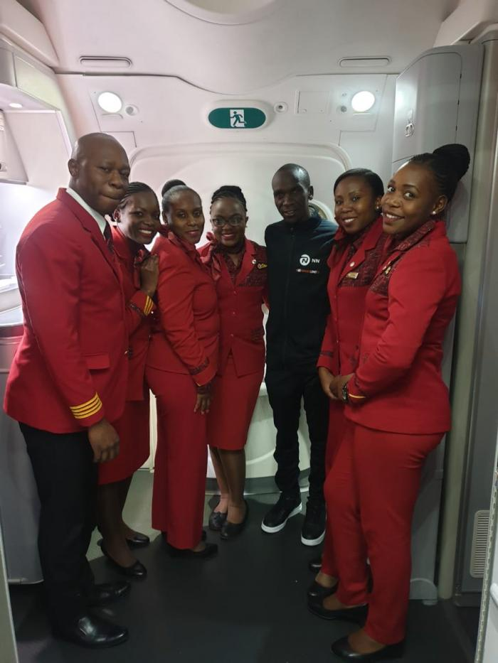 Marathon Champion Eliud Kipchoge (in black) with crew members from Kenya Airways during his trip from Vienna on Wednesday, October 16, 2019.