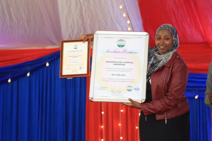 A Machakos county official displays the ISO certificate awarded to the Machakos level 5 hospital laboratory