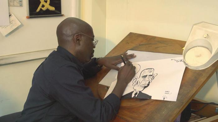 Gado going about his art business in a studio.