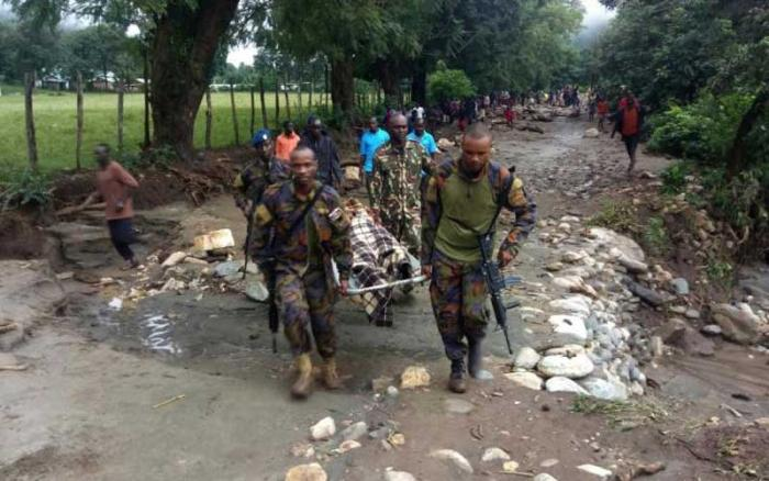 Administration policemen carry a recovered body after landslides hit two villages in West Pokot County on November 23