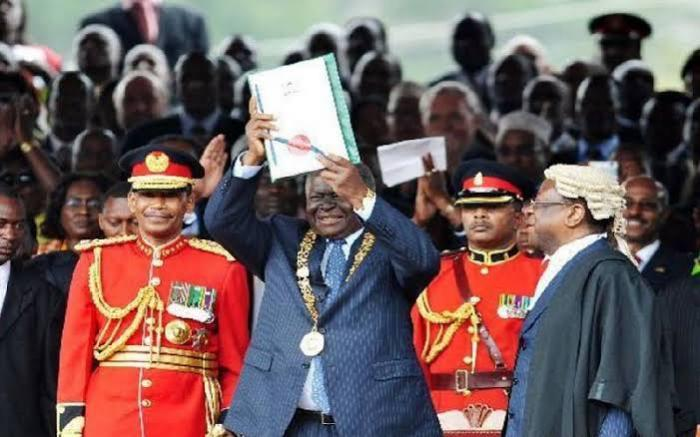 Former president Mwai Kibaki holds up the Kenyan Constitution on August 27, 2010.
