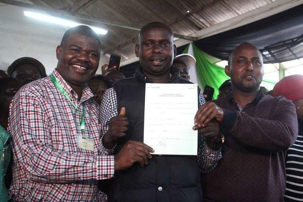 ODM politician Imran Okoth displays his certificate after winning the Kibra by-election, at the NCC Hall in Dagoretti on November 8, 2019, flanked by Ruaraka MP TJ Kajwang (L) and Suna East MP Junet Mohamed.