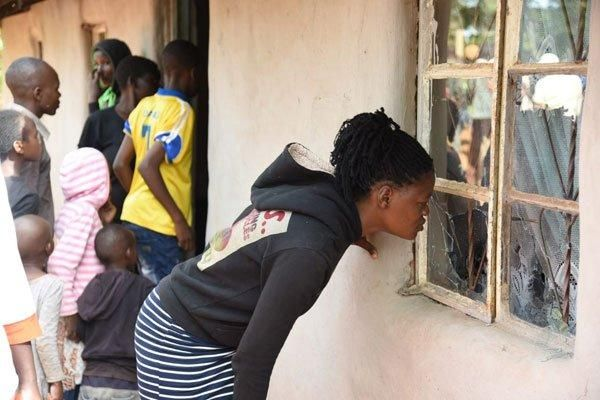 An Eldoret resident peeps through a broken window pane to see the inside of a house where a KDF soldier shot to death his relatives on April 30, 2019.