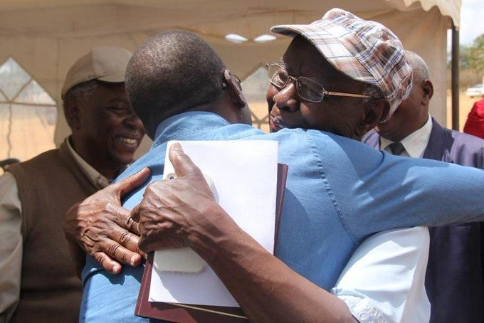 Prof Mbiti hugs former CJ willy Mutunga at AIC Mulango Primary school in Kitui county for the launch of his Kikamba Bible in March 2015.