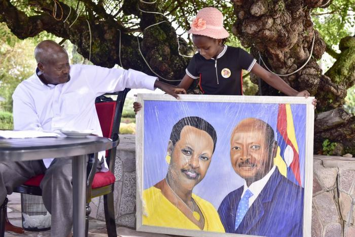 Sheldon hands Ugandan President Yoweri Museveni a portrait in April 2019
