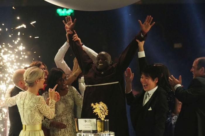 Peter Tabichi (c) reacts after winning the 2019 Global Teacher Prize in Dubai, the United Arab Emirates on March 24, 2019.