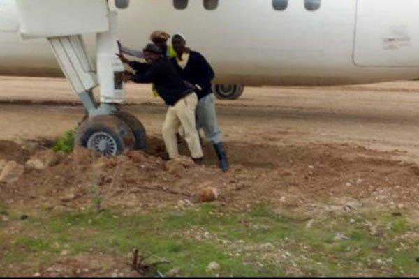 residents try to push the plane out of the Mud. It skid off the runway while taking off from the Takada airstrip in Mandera west on October 20