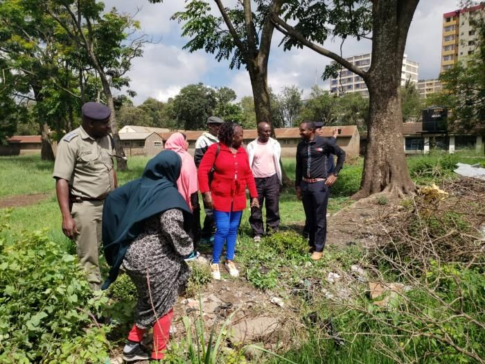 Police officers escort Boniface Mwangi and a group of activists as they reclaimed a section of Racecourse Primary school that had been grabbed, November 20, 2019.