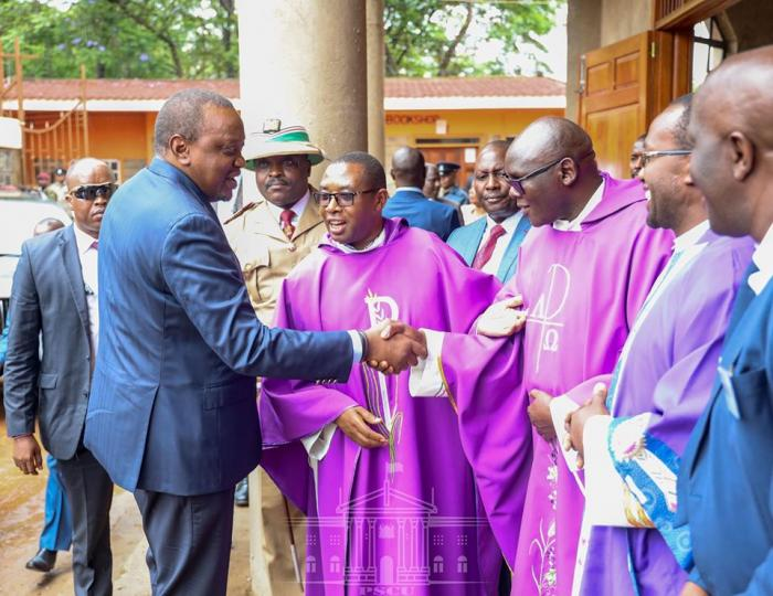 President Uhuru Kenyatta being introduced to members of the clergy by Father Paul Sila at the St. Francis of Asiss Parish Church in Kiambu on Sunday, December 8.