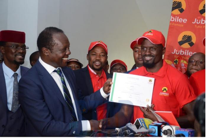 Jubilee Secretary-General, Raphael Tuju offering McDonald Mariga with the nomination certificate. IEBC barred Mariga from contesting