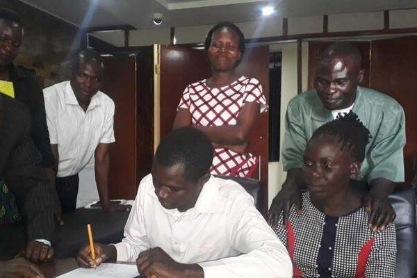 Kevin Barasa signs the agreement next to his former wife Lilian Weta