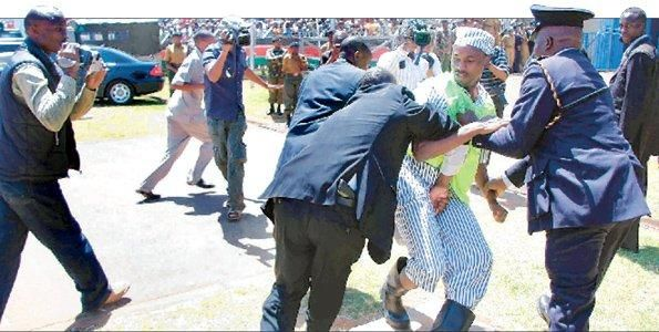 Comedian Walter Mong'are, better known as Nyambane, is manhandled by security officers at the Nyayo Stadium on December 12, 2008, as he protested against a media law passed by Parliament.