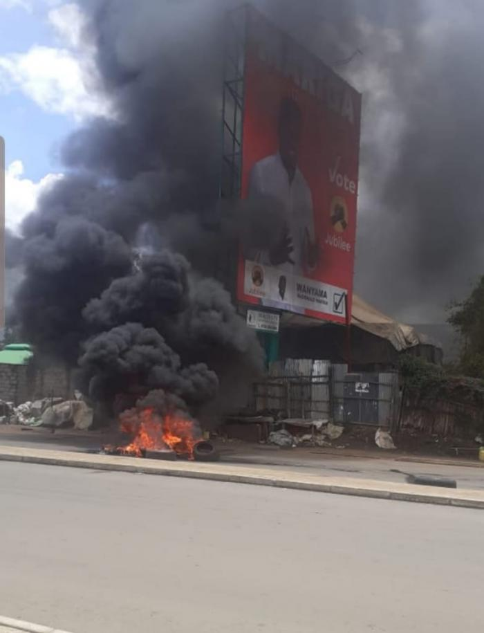 Tyres belonging to Mariga's campaign vehicle being burnt alongside his billboard (Courtesy)