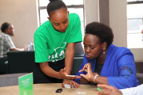 Safaricom Brand Ambassador Instructing a Safaricom customer during the launch of revamped PostPay bundles in Nairobi on March 3, 2020