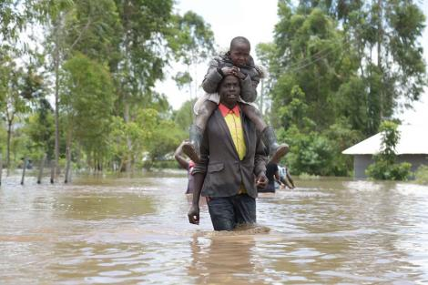 A man crosses through floodwaters in Nyando on Tuesday, April 21, 2020, while carrying a child.