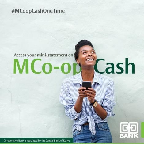 A model standing in front of an Mco-op Cash banner.