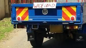A pickup truck displaying the 'Wide Load' signage.