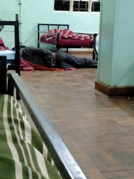 A quarantined individual sleeping on the floor at Kenya High School.