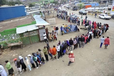 An image of people queuing up to vote