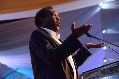 Political analyst Herman Manyora gestures while delivering an address at a past event