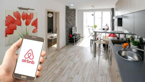 A photo of someone holding a phone with an Airbnb logo in a living room
