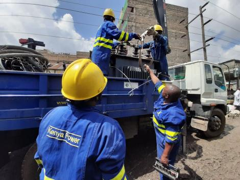Kenya Power and Lighting Company engineers load a transformer unto a lorry.