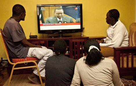 Kenyans watching proceedings on a TV screen.