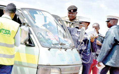 NTSA officials accompanied by police inspect a matatu in Nairobi in December 2019
