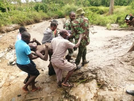 Police officer and local residents rescue a man who was trapped following the landslide that hit West Pokot County on April 18, 2020.