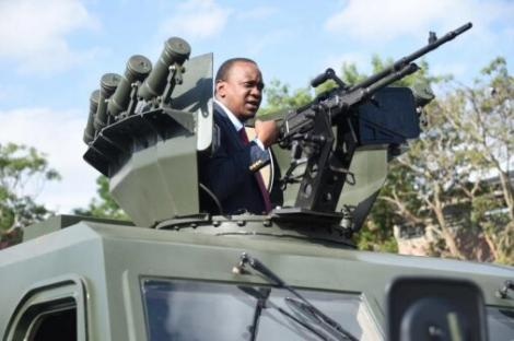 President Uhuru Kenyatta inspects a gun mounted on top of an Armoured Personnel Carrier (APC) when he commissioned APCs for the Kenya Police Service at G.S.U