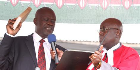 Siaya Governor Cornel Rasanga Amoth (left) takes the oath of office when he was sworn-in by Justice Aggrey Muchelule at Siaya Stadium in 2013